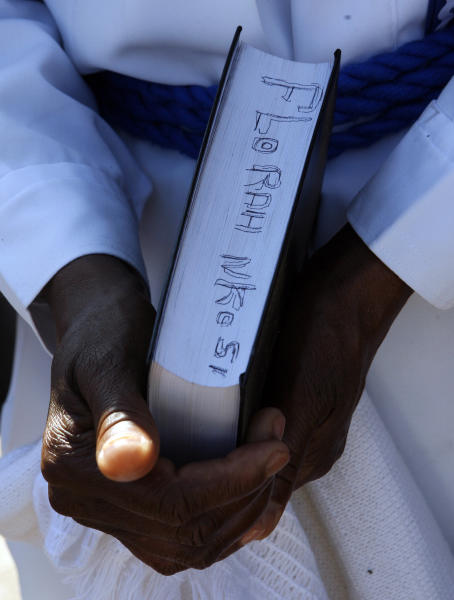 A wellwisher Florah Nkosi holds a bible as she prays outside the Mediclinic Heart Hospital where former South African President Nelson Mandela is being treated in Pretoria, South Africa Wednesday, June 26, 2013. South Africa's president Jacob Zuma on Tuesday urged his compatriots to show their appreciation for Nelson Mandela, who is in critical condition in a hospital, by marking his 95th birthday next month with acts of goodness that honor the legacy of the anti-apartheid leader. (AP Photo/Themba Hadebe)