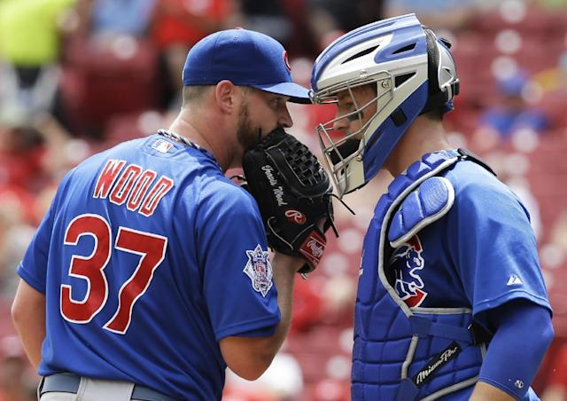Chicago Cubs starting pitcher Travis Wood (37) talks with catcher John Baker in the fifth inning of a baseball game against the Cincinnati Reds, Tuesday, July 8, 2014, in Cincinnati. (AP Photo/Al Behrman)