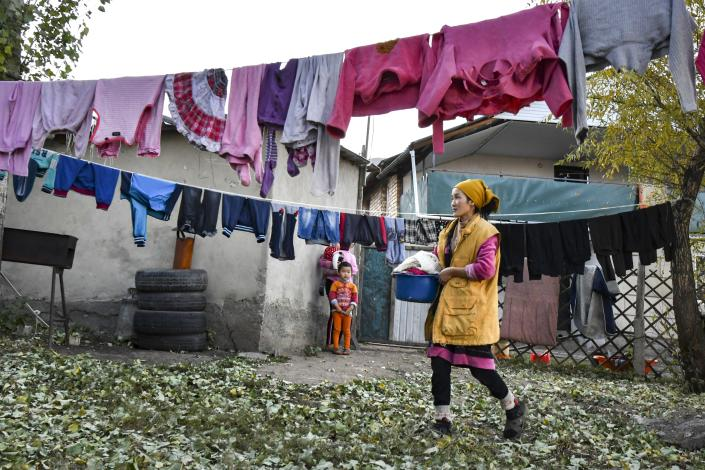 Burul, wife of Kanat Kaliyev's son Adilet, hangs up the laundry to dry at a yard of their family house in Tash Bashat village about 24 kilometers (15 miles) southeast of Bishkek, Kyrgyzstan, Tuesday, Oct. 20, 2020. Political turmoil has gripped Kyrgyzstan over recent years, but life in this quiet village nestled between scenic mountains follows its centuries-old course. (AP Photo/Vladimir Voronin)