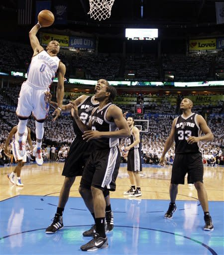 Oklahoma City Thunder point guard Russell Westbrook (0) dunks as San Antonio Spurs center Tim Duncan (21), small forward Kawhi Leonard (2) and power forward Boris Diaw (33), of France, watch during the first half of Game 6 in the NBA basketball Western Conference finals, Wednesday, June 6, 2012, in Oklahoma City. (AP Photo/Eric Gay)