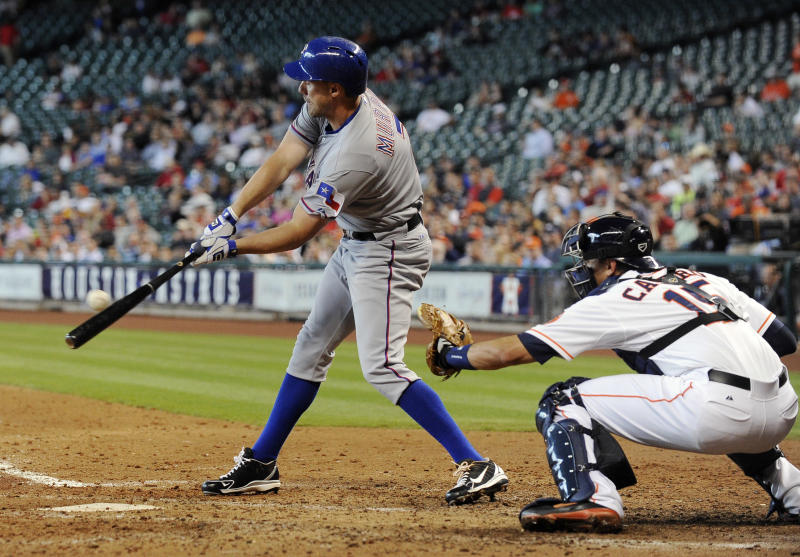 Texas Rangers' David Murphy, left, connects for an RBI-single with the bases loaded as Houston Astros catcher Jason Castro waits for the pitch in the sixth inning of a baseball game on Wednesday, April 3, 2013, in Houston. (AP Photo/Pat Sullivan)