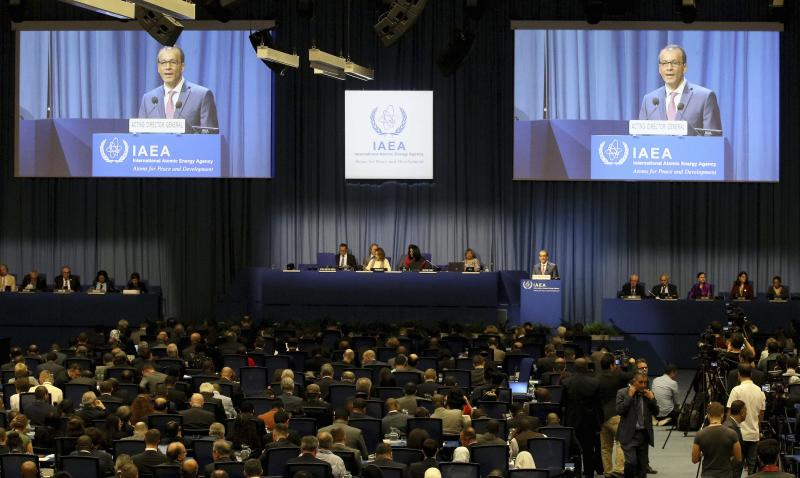 Acting Director General of the International Atomic Energy Agency, IAEA, Cornel Feruta from Romania is seen on screens as he delivers a speech at opening of the general conference of the IAEA, at the International Center in Vienna, Austria, Monday, Sept. 16, 2019. (AP Photo/Ronald Zak)