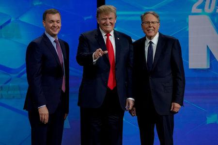 FILE PHOTO: U.S. President Donald Trump is greeted by Chris Cox (L) and Wayne LaPierre (R), executive vice president and CEO of the National Rifle Association (NRA), at the NRA annual meeting in Indianapolis, Indiana, U.S., April 26, 2019. REUTERS/Bryan Woolston/File Photo