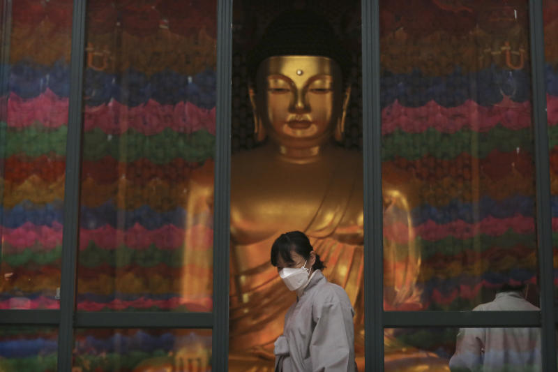 """A Buddhist believer wearing a face mask leaves the Jogyesa Buddhist temple in Seoul, South Korea, Tuesday, Feb. 25, 2020. South Korea reported another large jump in new virus cases Monday a day after President Moon Jae-in called for """"unprecedented, powerful"""" steps to combat the outbreak that is increasingly confounding attempts to stop the spread.(AP Photo/Ahn Young-joon)"""