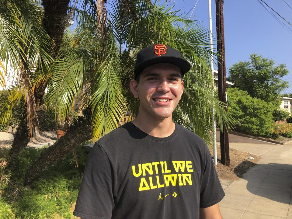 """Bradley Pierce, 21, poses for a photo Tuesday, Sept. 14, 2021, outside a San Diego polling site after voting no to recall California Gov. Gavin Newsom. Pierce, a registered Independent who leans liberal, said he made sure to vote because he was """"unnerved"""" by the prospect of the state falling into Republican hands. (AP Photo by Julie Watson)"""