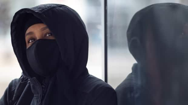 A person wearing a mask sits in a bus shelter in late April 2021. On Sunday, Ottawa's health officials reported 143 new cases of COVID-19 and two deaths.  (Andrew Lee/CBC - image credit)