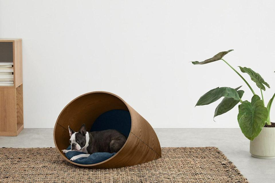 """<p>With its natural walnut frame and navy cushions, the 'Kyali' bed has a sleek, architectural feel that will fit naturally in any contemporary interior. It's easy to keep clean (the cushion covers are removable) and gives pets a cosy, cocooning sanctuary to call their own. £169, <a href=""""https://www.made.com/"""" rel=""""nofollow noopener"""" target=""""_blank"""" data-ylk=""""slk:made.com"""" class=""""link rapid-noclick-resp"""">made.com</a></p>"""