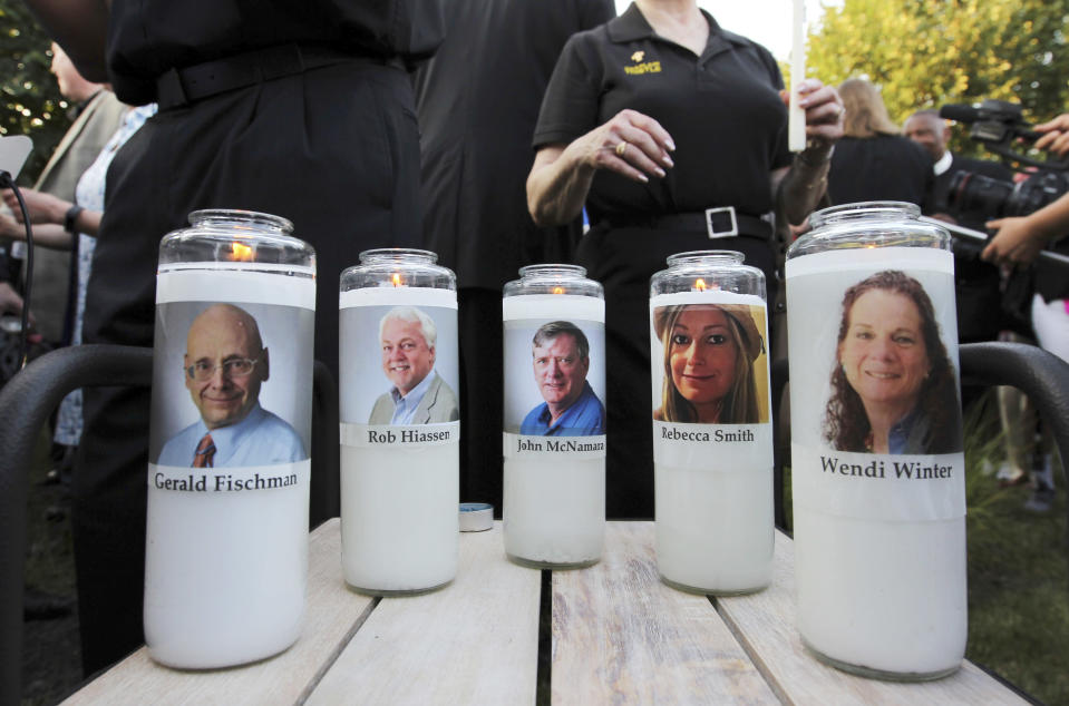 FILE - In this June 29, 2018, file photo, pictures of five employees of the Capital Gazette newspaper adorn candles during a vigil across the street from where they were slain in the newsroom in Annapolis, Md. A jury was selected on Friday, June 25, 2021, for the second phase of a trial for a man who killed the five people at the newspaper to decide whether he is criminally responsible due to his mental health. Jarrod Ramos pleaded guilty in 2019 to all 23 counts against him in the attack at the Capital Gazette nearly three years ago, but he has pleaded that he is not criminally responsible due to mental illness. (AP Photo/Jose Luis Magana, File)