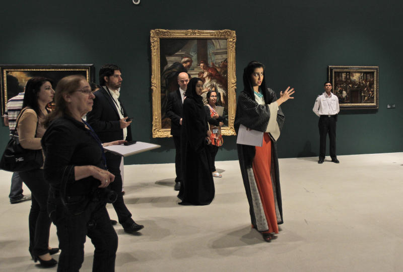 An Emirati guide, middle, talks about the paintings during a visit to a sample collection at the Abu Dhabi branch of the Louvre in Abu Dhabi, United Arab Emirates, Tuesday, April 16, 2013. No artistic subjects will be off limits at the Abu Dhabi branch of the Louvre museum as it builds its collection for a planned 2015 opening, a top overseer said Tuesday, in a city seeking to broaden its international profile but testing how far to open its conservative culture. (AP Photo/Kamran Jebreili)
