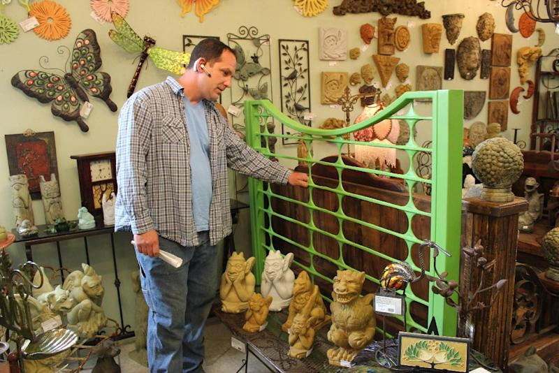 In this May 19, 2012 photo, Jim Honold, the owner of Home & Garden Art in Seattle, points out his hand-crafted modern gate, among a room of sculptures and outdoor art. Honold recommends an artistic gate to reflect personality and set the tone for the rest of the house. (AP Photo/Cedar Burnett)