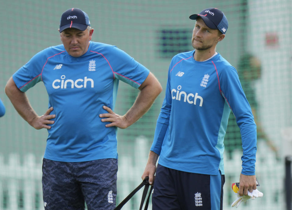FILE - In this file photo taken on Aug. 10, 2021, England's cricket coach Chris Silverwood, left, speaks his team captain England's Joe Root during a practice session in London. England have named a 17-man squad for this winter's Ashes tour, with head coach Chris Silverwood leaning on familiar faces for the trip. Silverwood and captain Joe Root are unable to call on a full-strength group due to the continued hiatus of star all-rounder Ben Stokes and injuries to Jofra Archer, Olly Stone and Sam Curran but fears over players opting out due to concerns over Australia's travel restrictions have not materialized. (AP Photo/Alastair Grant)