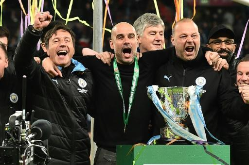 Three and easy: Manchester City manager Pep Guardiola (centre) celebrates a third straight League Cup win
