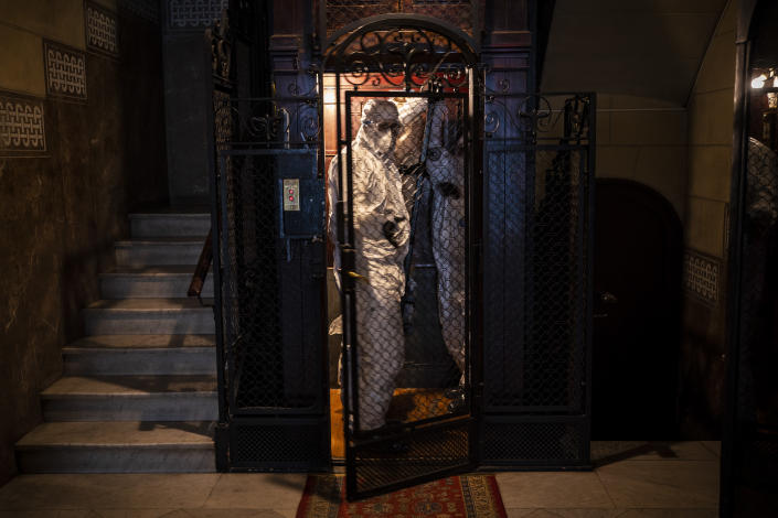 Wearing protective suits to prevent infection, mortuary workers move the body of an elderly person who died of COVID-19 from an elevator after removing it from a nursing home in Barcelona, Spain, Nov. 13, 2020. The image was part of a series by Associated Press photographer Emilio Morenatti that won the 2021 Pulitzer Prize for feature photography. (AP Photo/Emilio Morenatti)