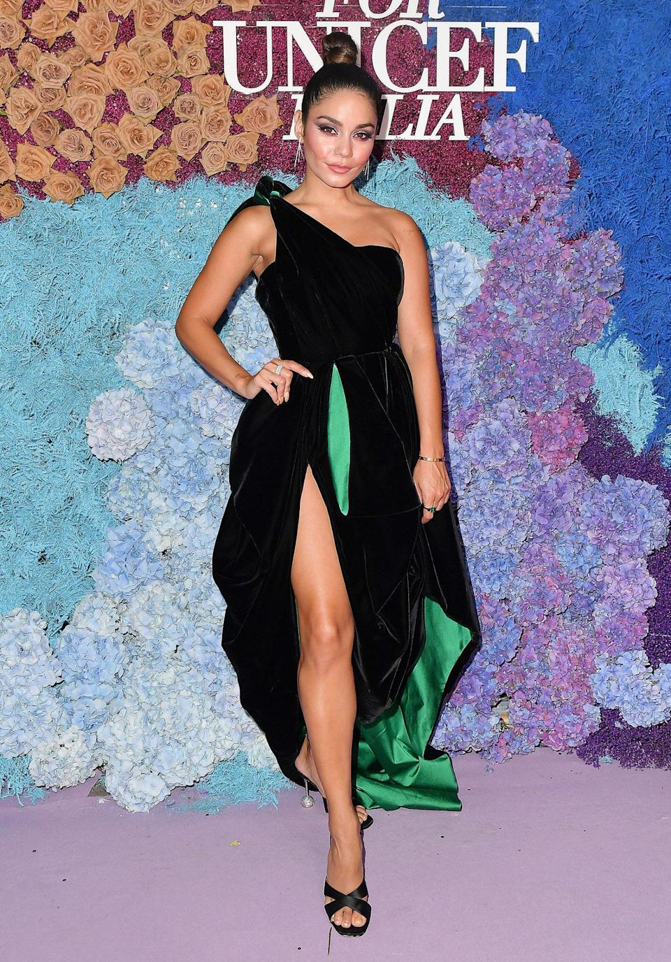 <p>in a one-shoulder black gown with green lining, plus drop earrings and black heels. </p>