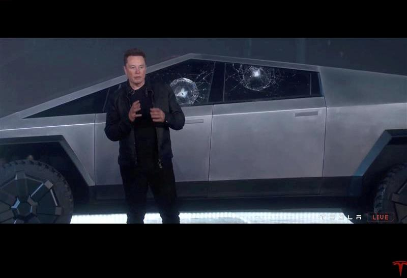 FILE PHOTO: Tesla Chief Executive Elon Musk stands in front of the cracked windows of company's first electric pickup truck, the Cybertruck, after it was unveiled and a metal ball was thrown at the windows, in Los Angeles