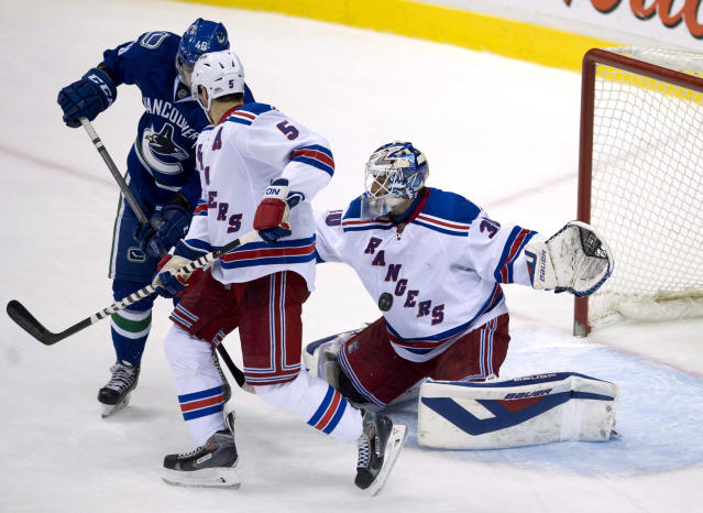 Vancouver Canucks left wing Nicklas Jensen (46) tries to get a shot past New York Rangers goalie Henrik Lundqvist (30) as Rangers defenseman Dan Girardi (5) watches during the second period of an NHL hockey game Tuesday, April 1, 2014, in Vancouver, British Columbia. (AP Photo/The Canadian Press, Jonathan Hayward)