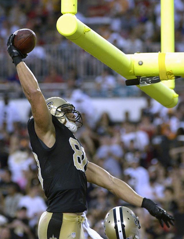 New Orleans Saints tight end Jimmy Graham prepares to dunk the football over the goalpost after scoring on a 56-yard touchdown pass from quarterback Drew Brees during the first quarter of an NFL football game against the Tampa Bay Buccaneers, Sunday, Sept. 15, 2013, in Tampa, Fla. (AP Photo/Phelan M. Ebenhack)
