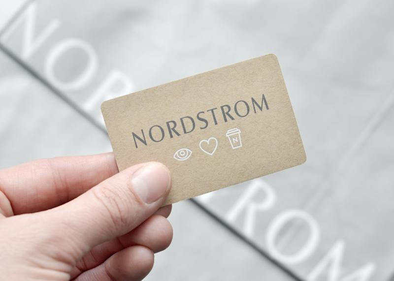 Vancouver, B.C., Canada -- February 4, 2015:Closeup of a man's hand holding a Nordstrom Gift Card above Nordstrom shopping bags. Nordstrom is the largest upscale fashion retailer in the United States.