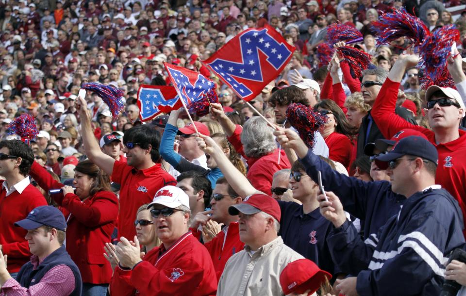 """In this Nov. 28, 2009 photograph, University of Mississippi fans wave the remodeled """"M"""" flag for the university in the stands at last year's Egg Bowl game against Mississippi State in Starkville, Miss. The university has been shedding Old South symbols for several years-- in 1997 the waving of Confederate flags at sporting events was banned, and Colonel Reb was nixed as the on-field mascot in 2003. Students vote Tuesday on a new mascot.  (AP Photo/Rogelio V. Solis)"""