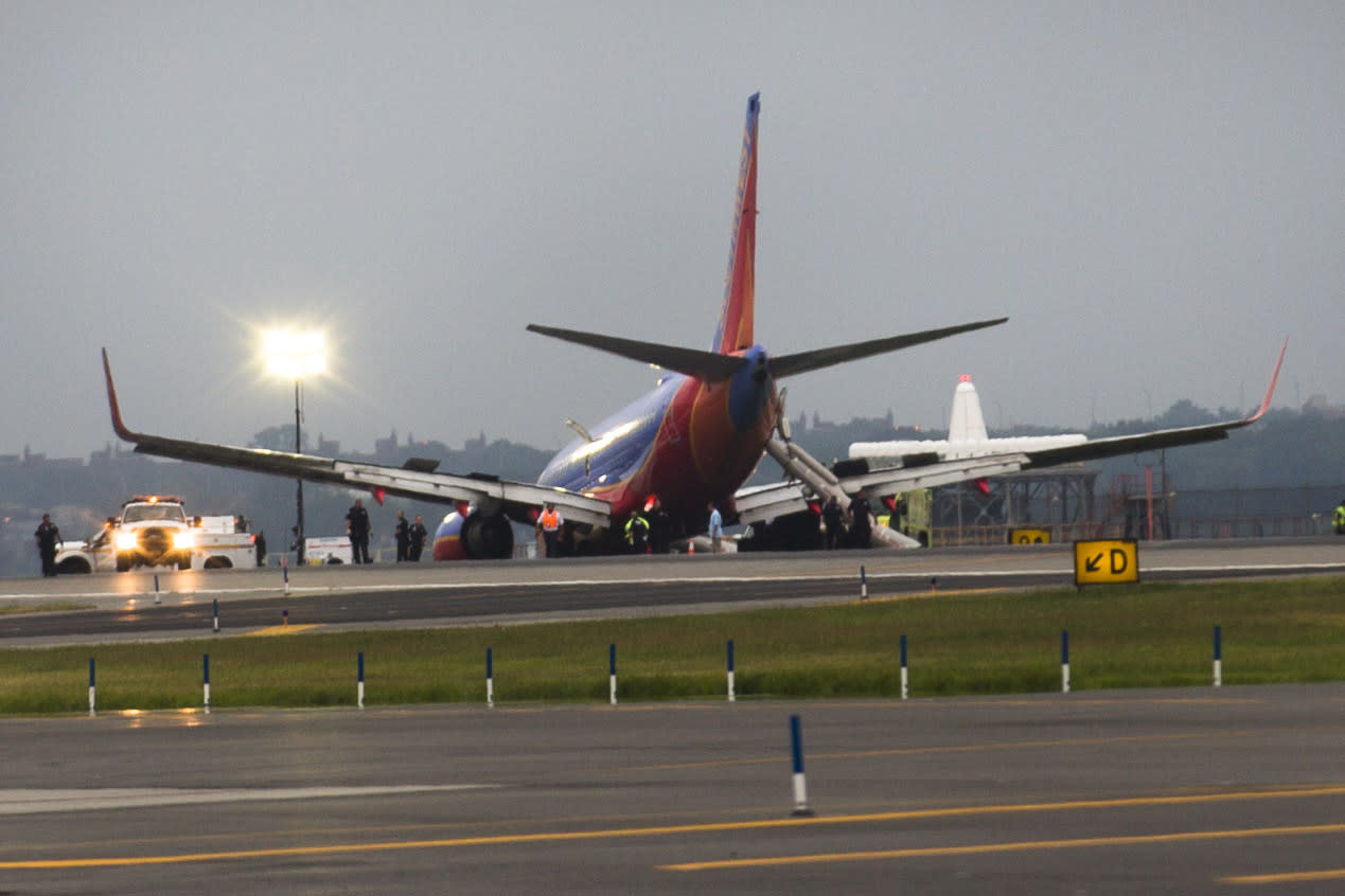 A southwest airlines plane rests on the tarmac after what officials say was a nose gear collapse during a landing at LaGuardia Airport, Monday, July 22, 2013, in New York. The Federal Aviation Administration says the plane landed safely. (AP Photo/John Minchillo)