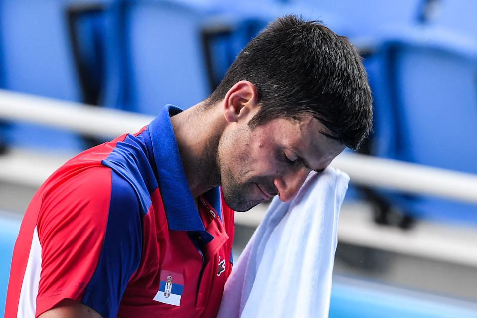 Serbia's Novak Djokovic wipes his face during his Tokyo 2020 Olympic Games men's singles tennis match for the bronze medal against Spain's Pablo Carreno Busta at the Ariake Tennis Park in Tokyo on July 31, 2021. (Photo by Tiziana FABI / AFP) (Photo by TIZIANA FABI/AFP via Getty Images)