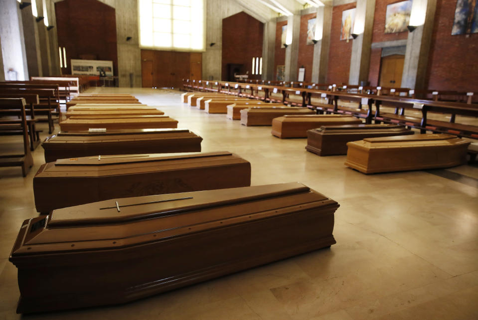 """FILE - In this March 26, 2020 file photo, coffins are lined up on the floor in the San Giuseppe church in Seriate, one of the areas worst hit by coronavirus, near Bergamo, Italy, waiting to be taken to a crematorium. After the European Union passed the death toll of half a million citizens lost to the coronavirus on Wednesday, Feb. 10, 2021, the EU Commission chief said that stalling rollout of the vaccines could be partly blamed on the bloc being over-optimistic, over-confident and plainly """"too late."""" (AP Photo/Antonio Calanni, File)"""