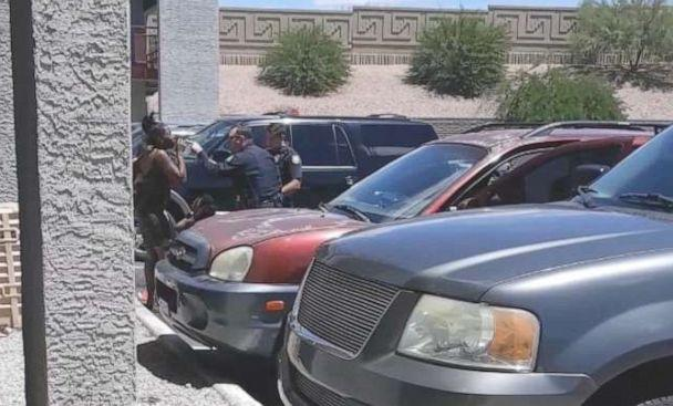 PHOTO: Cell phone video shows officers from the Phoenix Police Department after sweep-kicking handcuffed Dravon Ames and pointing a gun at a pregnant mother with her two young daughters, May 27, 2019. (Obtained by ABC News)