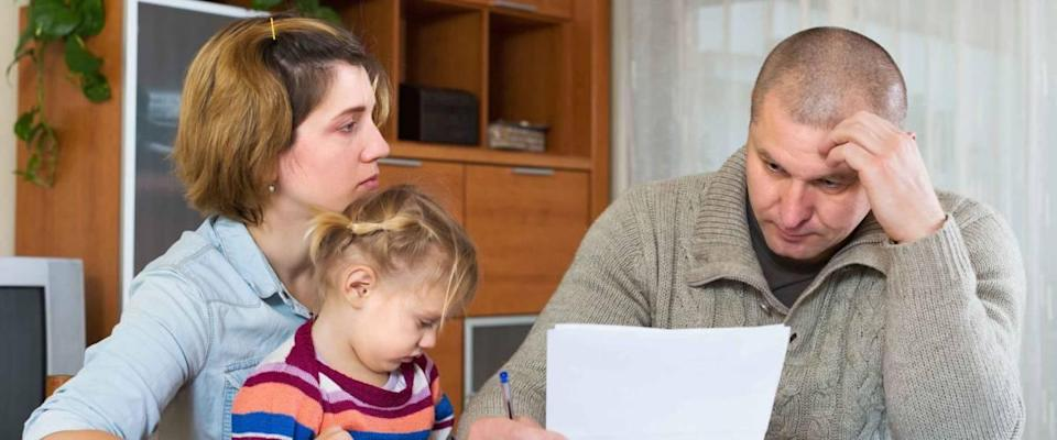 Serious couple with little girl counting budget at home