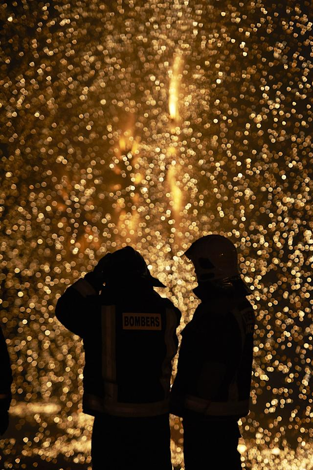 VALENCIA, SPAIN - MARCH 19:  Firemen look on while a combustible 'Ninot' caricatures burn during the last day of the 'Fallas' festival on March 19, 2012 in Valencia, Spain.  The festival, which runs March 15 - 19, celebrates the arrival of spring with fireworks, fiestas and bonfires. (Photo by Xaume Olleros/Getty Images)