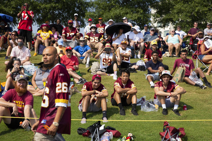 """FILE - Washington Football Team fans watch drills during NFL football practice in Richmond, Va., in this Wednesday, July 28, 2021, file photo. It's not exactly everyone into the pool, or gathering around the bonfire. The NFL's """"Back Together Saturday"""" at training camps is all about football. Well, also about having fans return to watch, with all 32 teams conducting open practices on Saturday as part of a unified effort by the league. (AP Photo/Ryan M. Kelly, File)"""