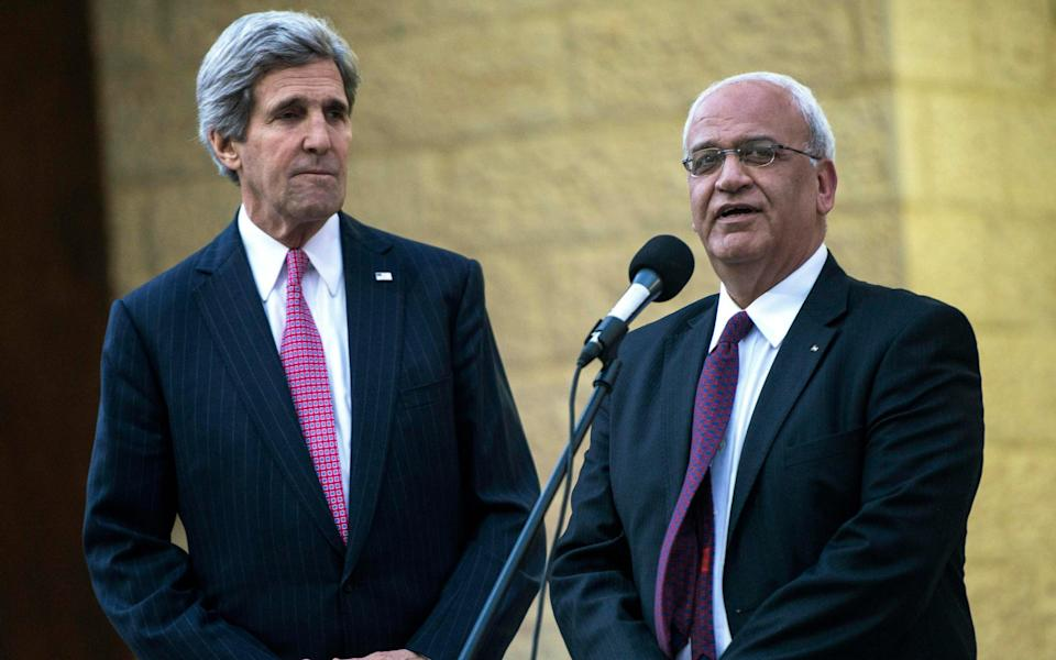 File image from 2014 where US Secretary of State John Kerry, left, listens to Palestinian negotiator Saeb Erekat - Brendan Smialowski/ AFP