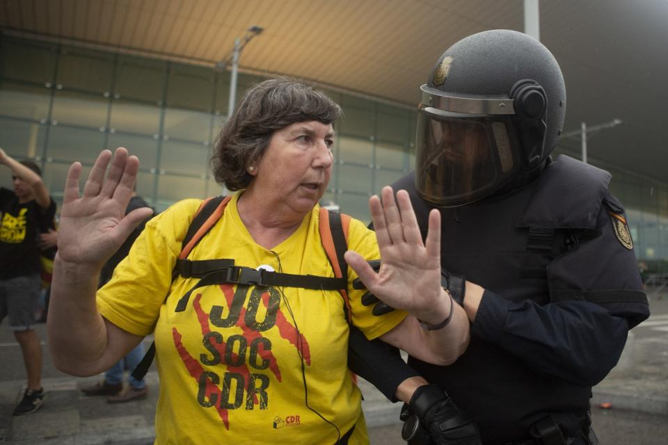 In this Monday, Oct. 14, 2019 photo, a Spanish police talks to a pro-independence protester during a demonstration at El Prat airport, outskirts of Barcelona, Spain. Riot police engaged in a running battle with angry protesters outside Barcelona's airport Monday after Spain's Supreme Court convicted 12 separatist leaders of illegally promoting the wealthy Catalonia region's independence and sentenced nine of them to prison. (AP Photo/Joan Mateu)
