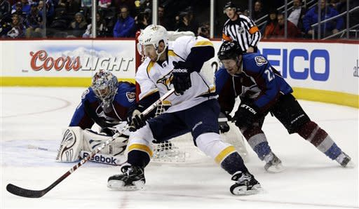 Nashville Predators defenseman Jonathon Blum (7) circles the net against Colorado Avalanche right wing Milan Hejduk (23), of the Czech Republic, and goalie Semyon Varlamov (1), of Russia, during the second period of an NHL hockey game, Monday, Feb. 18, 2013, in Denver.(AP Photo/Joe Mahoney)