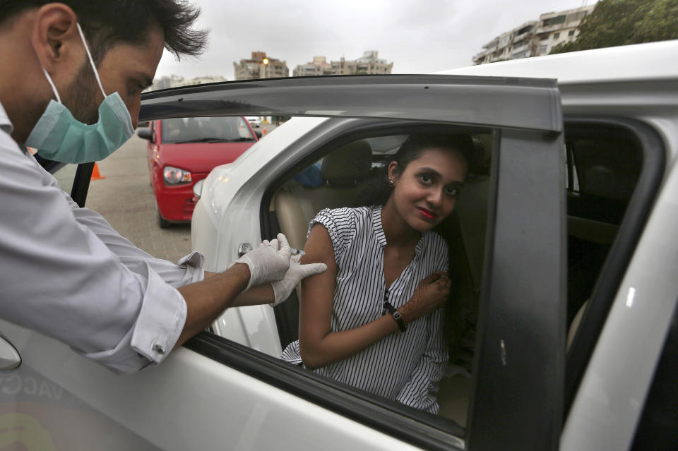 A woman receives the Sinovac COVID-19 vaccine from a health worker at a drive-through vaccination center, in Karachi, Pakistan, Saturday, July 31, 2021. (AP Photo/Fareed Khan)