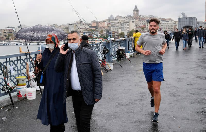 FILE PHOTO: People wearing protective masks walk over the Galata Bridge in Istanbul