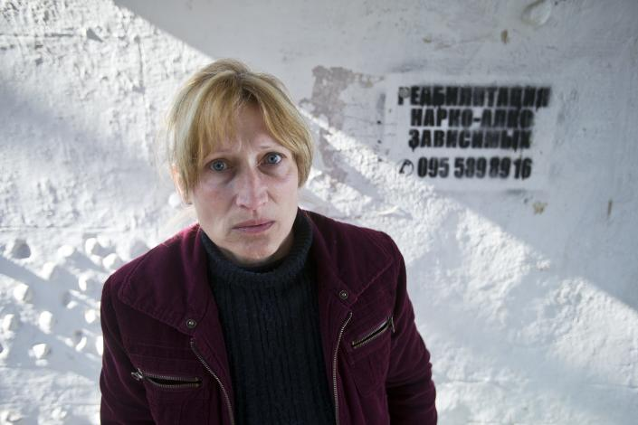 """In this photo taken Tuesday, April 1, 2014, Svetlana Starikova, a patient of treatment for drug addiction, poses at a bus stop with an advert reading """"Rehabilitation of drug and alcohol addicts"""" in Sevastopol, Crimea. Across the Black Sea peninsula, some 800 heroin addicts and other needle-drug users take part in methadone programs, seen as an important part of efforts to curb HIV infections by taking the patients away from hypodermic needles that can spread the AIDS-causing virus. After Russia's annexation of Crimea methadone was banned. The ban could undermine years of efforts to reduce the spread of AIDS in Crimea. (AP Photo/Pavel Golovkin)"""
