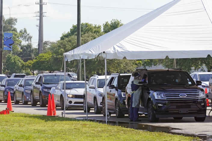 Cars line up at Miami Dade College North campus' COVID-19 testing site, Thursday, July 29, 2021, in Miami. Hospital admissions of coronavirus patients continue to soar in Florida with at least two areas in the state surpassing previous peaks reached during last summer's surge. (AP Photo/Marta Lavandier)