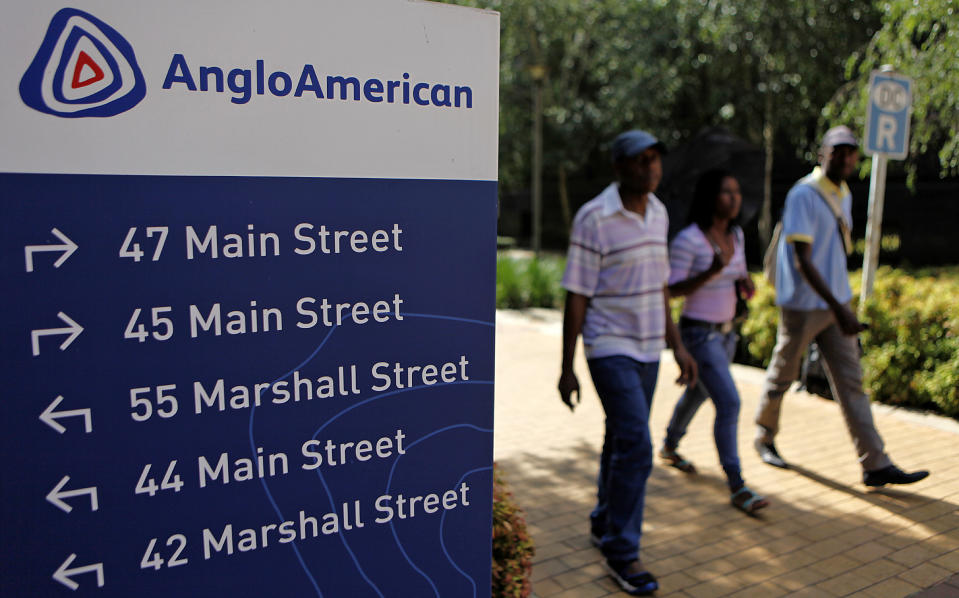 People walk past a board outside the Anglo American offices in Johannesburg, South Africa. Photo: Siphiwe Sibeko/Reuters