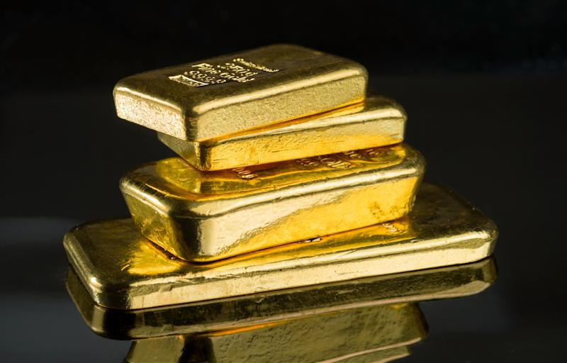 Several gold bars of different weight on a dark mirror surface