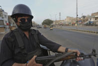 A police officer take position on a vehicle at a deserted road due to strikes called by the the country's religious political parties over the security forces's crackdown against a banned Tehreek-e-Labaik Pakistan party, in Karachi, Pakistan, Monday, April 19, 2021. An outlawed Pakistani Islamist political group freed 11 policemen almost a day after taking them hostage in the eastern city of Lahore amid violent clashes with security forces, the country's interior minister said Monday. (AP Photo/Fareed Khan)