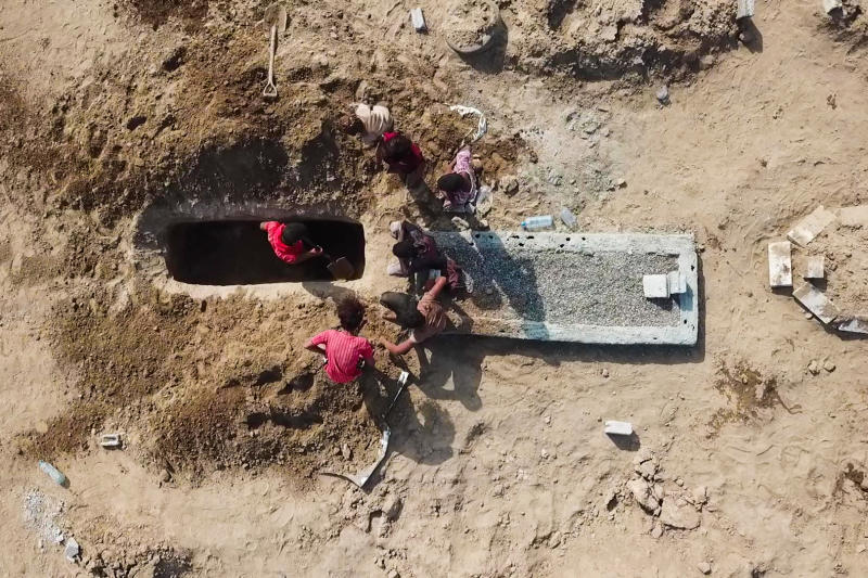 In this May 21, 2020, photo, grave diggers bury a body at Radwan Cemetery in Aden, Yemen. At a cemetery in Yemen's largest southern city, dozens of fresh graves are a testament to a spike in deaths amid the coronavirus pandemic. The cemetery workers who bury them don't know what killed the newly deceased. But there's no denying that there's been an increasing number of people getting sick in the port city of Aden — likely from the coronavirus. (AP Photo)