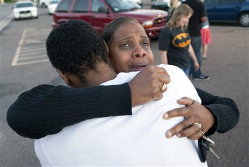 "Shamecca Davis hugs her son Isaiah Bow, who was an eye witness to the shooting, outside Gateway High School where witness were brought for questioning Friday, July 20, 2012 in Denver. After leaving the theater Bow went back in to find his girlfriend. "" I didn't want to leave her in there. But she's ok now,"" Bow said. A gunman wearing a gas mask set off an unknown gas and fired into a crowded movie theater at a midnight opening of the Batman movie ""The Dark Knight Rises,"" killing at least 12 people and injuring at least 50 others, authorities said. (AP Photo/Barry Gutierrez)"