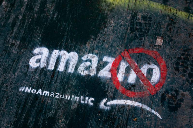 Graffiti has been painted on a sidewalk by someone opposed to the location of an Amazon headquarters in the Long Island City neighborhood in the Queens borough of New York, Friday, Nov. 16, 2018. Residents of the New York City public housing complex near the spot where Amazon plans to put a new headquarters have mixed reaction to the global behemoth coming to the neighborhood. (AP Photo/Mark Lennihan)