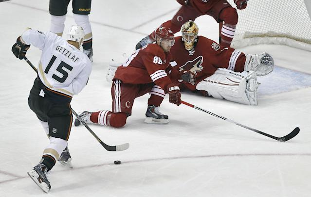 Anaheim Ducks' Ryan Getzlaf (15) scores against Phoenix Coyotes goalie Thomas Greiss and Mikkel Boedker (85) during the second period of an NHL hockey game, Saturday, Jan. 11, 2014, in Glendale, Ariz. (AP Photo/Matt York)