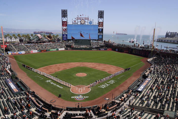 The San Francisco Giants, left, and the Colorado Rockies stand along the baselines during an opening day flyover before their baseball game Friday, April 9, 2021, in San Francisco. (AP Photo/Eric Risberg)
