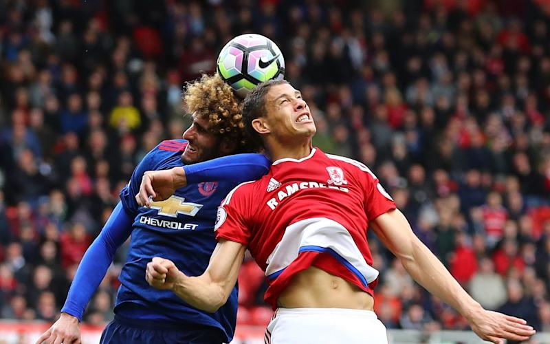 Marouane Fellaini of Manchester United (L) and Rudy Gestede of Middlesbrough (R) battle to win a header - Credit: Getty