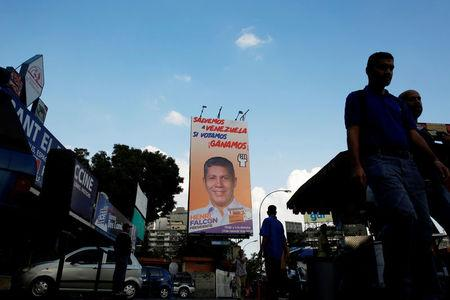 FILE PHOTO: People walk pass a campaign poster of Henri Falcon for the 2018 presidential elections in Caracas, Venezuela May 11, 2018. REUTERS/Carlos Jasso/File Photo