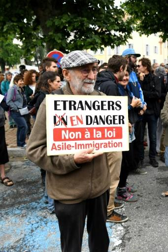 """Many people are unhappy with the French government's bid to introduce tough new immigration legislation, such as this protester holding a sign reading: """"Foreigners in danger, no to the asylum-immigration law"""""""