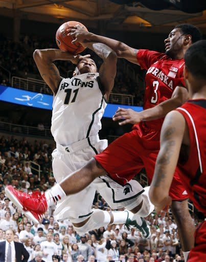 Michigan State's Keith Appling (11) is fouled by Nebraska's Benny Parker (3) as he drives to the basket during the second half of an NCAA college basketball game, Sunday, Jan. 13, 2013, in East Lansing, Mich. Michigan State won 66-56. (AP Photo/Al Goldis)