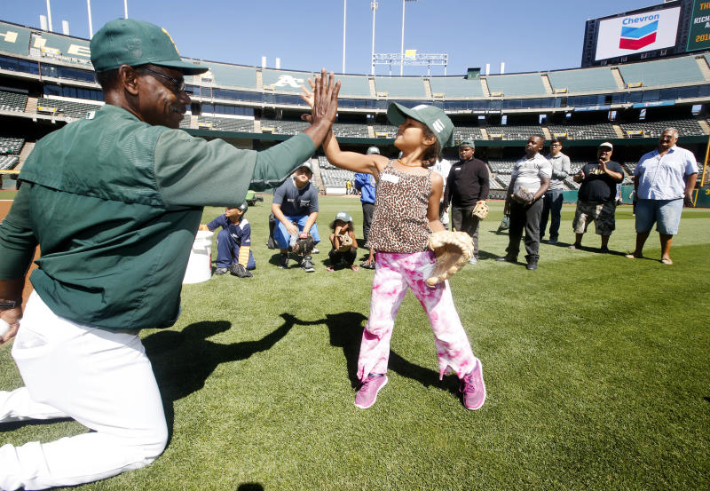 Oakland A's coach Ron Washington, left, high fives a young girl after teaching fielding to a group of Richmond, Calif. youth during a Chevron and Oakland A's youth baseball clinic at the O.co Coliseum on Thursday, July 21, 2016 in Oakland, Calif. Today, Chevron and Oakland Athletics teamed up to host a baseball clinic for Richmond youth to inspire science, technology, engineering and math (STEM) learning through the science of sports as part of Chevron's commitment to equipping youth with the critical skills they will need to succeed in jobs of the future. (Tony Avelar/AP Images for Chevron)